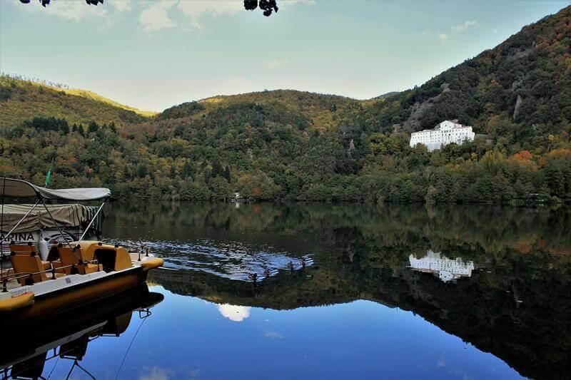 lago di Monticchio con visuale dell'Abazia di San Michele Arcangelo e pedalò sull'acqua