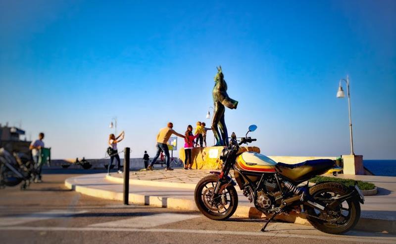 Ducati Scrambler parcheggiata ai piedi della Statua di Domenico Modugno sul lungomare di Polignano